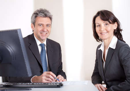 Two confident business people in the office at the meeting Stock Photo - 13907995