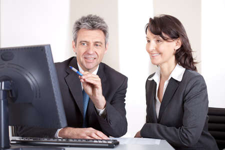senior business: Two confident business people in the office at the meeting