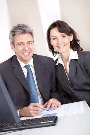 Two confident business people in the office at the meeting photo