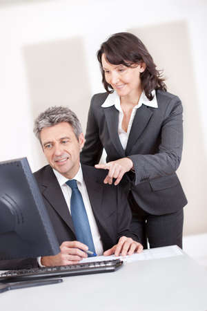 Manager overseeing businessman working on computer at the office Stock Photo - 13908026