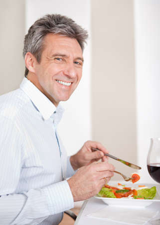Mature man having lunch together at home photo