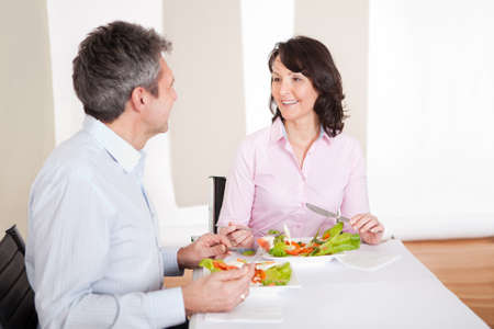 Mature couple having lunch together at home photo