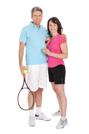 Mature couple with tennis racquets. Isolated on white photo