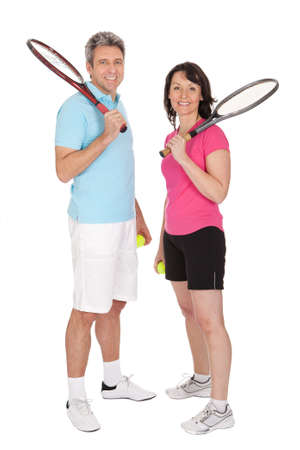 tennis racquet: Mature couple with tennis racquets. Isolated on white Stock Photo