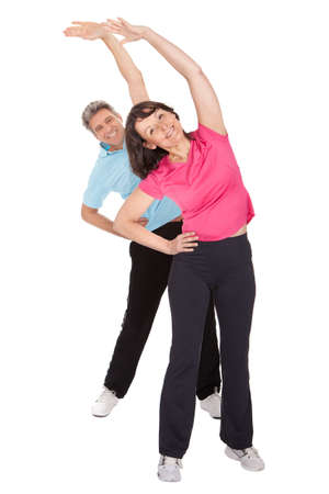 stretching: Active mature couple doing fitness. Isolated on white