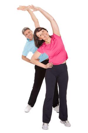 estiramientos: Pareja madura activo haciendo gimnasio. Aislado en blanco