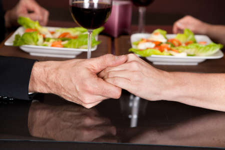 Mature couple touching hands at romantic dinner in restaurant photo