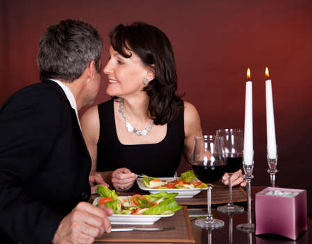 whispering: Mature couple having romantic dinner in restaurant Stock Photo