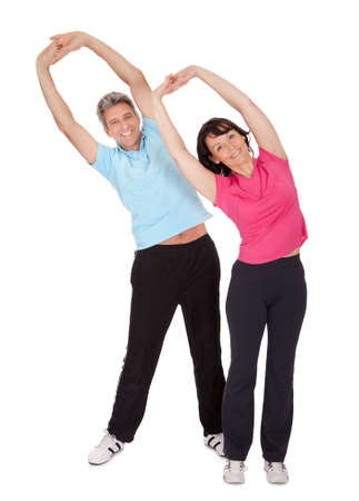 elderly exercise: Active mature couple doing fitness. Isolated on white