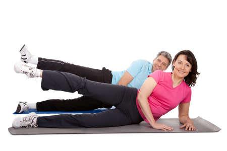 senior yoga: Active mature couple doing fitness. Isolated on white