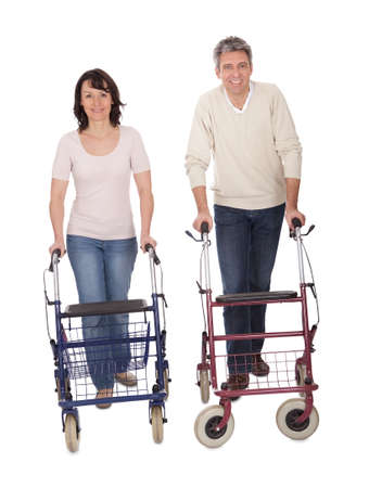 Mature couple using walking aide. Isolated on white photo