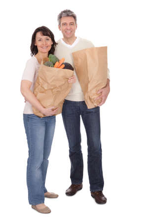 Happy couple with grocery shopping bags. Isolated on white photo