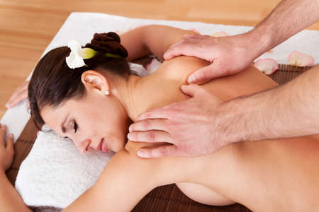 hand towel: Beautiful young woman getting back massage at spa Stock Photo