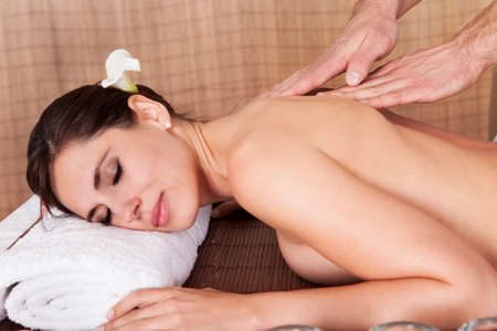 Beautiful young woman getting back massage at spa photo
