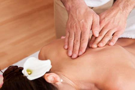 masaje deportivo: Joven y bella mujer recibiendo masaje de espalda en el spa