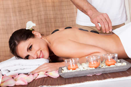 Beautiful young woman getting hot stone therapy at spa salon Stock Photo - 14011834