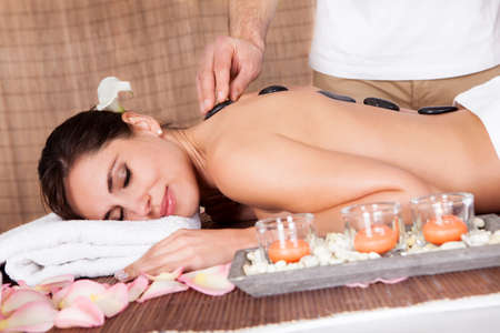 hot rock therapy: Beautiful young woman getting hot stone therapy at spa salon