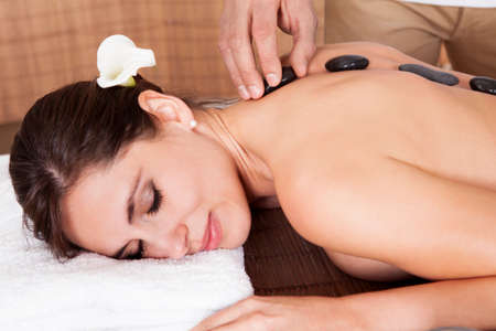 Beautiful young woman getting hot stone therapy at spa salon Stock Photo - 14011822