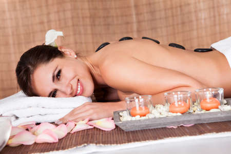 Beautiful young woman getting hot stone therapy at spa salon Stock Photo - 14011795