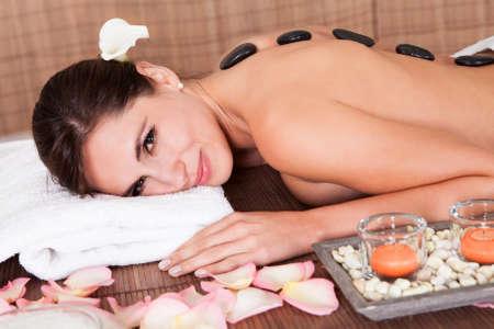massage oil: Belle jeune femme se massage aux pierres chaudes dans le salon de spa Banque d'images
