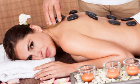 Beautiful young woman getting hot stone therapy at spa salon Stock Photo - 14011788