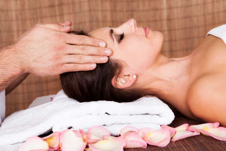 Beautiful young woman getting face massage at spa photo