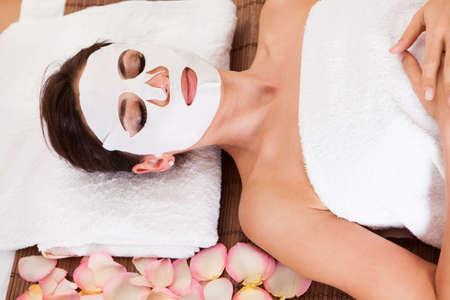 masked woman: Joven y bella mujer recibiendo la m�scara facial en el spa de estudio