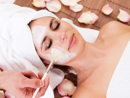 facial cleansing: Beautiful young woman getting facial mask at spa studio