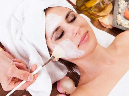 gezichtsbehandeling: Mooie jonge vrouw krijgt gezichtsmasker in de spa van studio