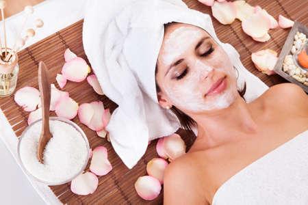 tratamiento facial: Joven y bella mujer recibiendo la máscara facial en el spa de estudio