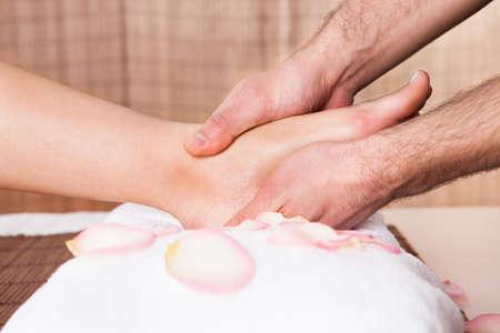 Beautiful young woman getting feet massage treatment at spa Stock Photo - 14017106