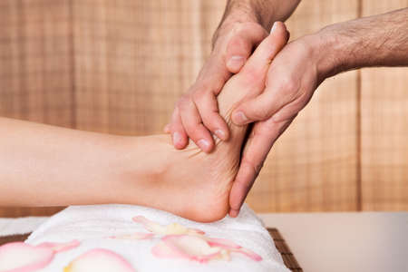 Beautiful young woman getting feet massage treatment at spa Stock Photo - 14018147