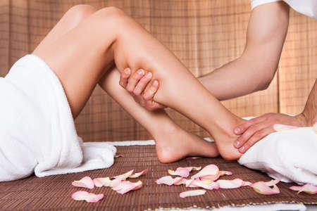 massage herbal: Beautiful young woman getting feet massage treatment at spa