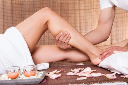 leg massage: Beautiful young woman getting feet massage treatment at spa