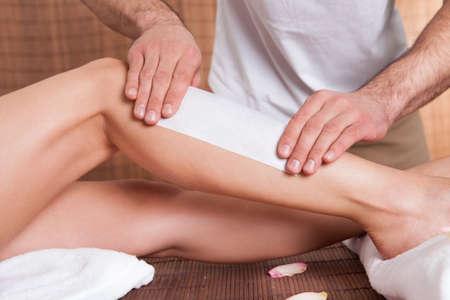 depilacion con cera: Est�tica haciendo la depilaci�n para la mujer joven en el sal�n del balneario