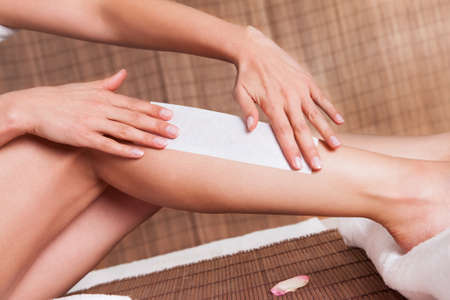 waxing: Close-up on young woman doing depilation on legs