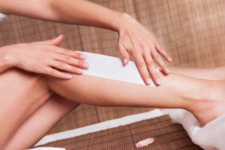 depilacion con cera: Primer plano de una mujer joven que hace la depilaci�n en las piernas