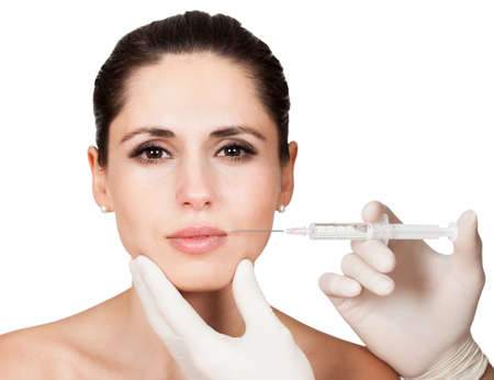 Beautician doing injection to the beautiful female face photo
