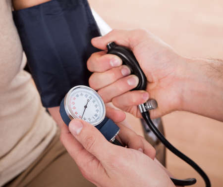Doctor checking blood pressure of a woman. Close-up shot Stock Photo - 14017103