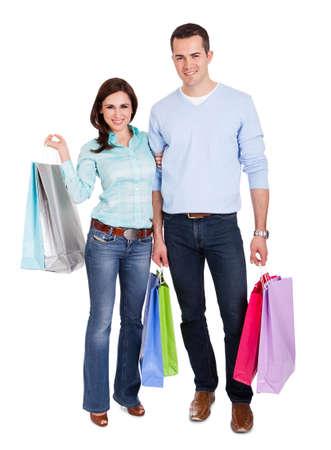 買い物袋と美しい若いカップル。白で隔離されます。 写真素材
