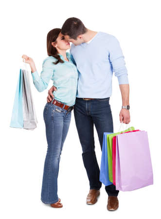 sexy couple kissing: Beautiful young couple with shopping bags. Isolated on white