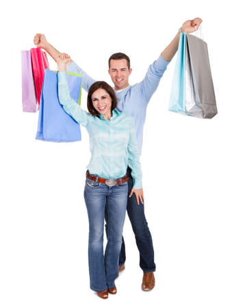 Beautiful young couple with shopping bags. Isolated on white photo