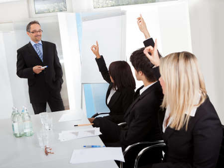 Group of business people at presentation raising hands in the office photo