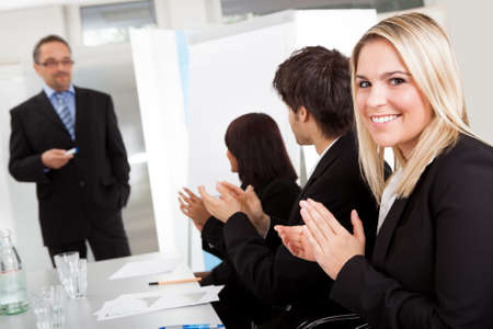 Portrait of businesswoman at presentation applauding to the lecturer photo