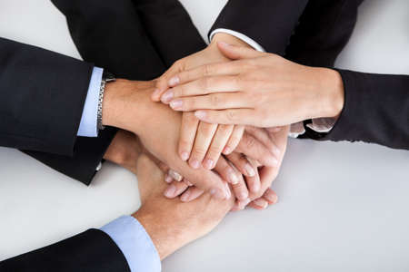 staff team: Closeup of a business colleagues with their hands stacked together Stock Photo