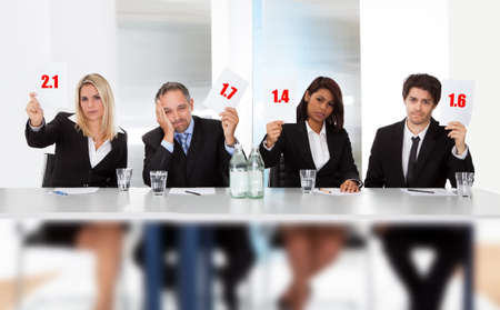 mistake: Group of panel judges holding bad score signs Stock Photo