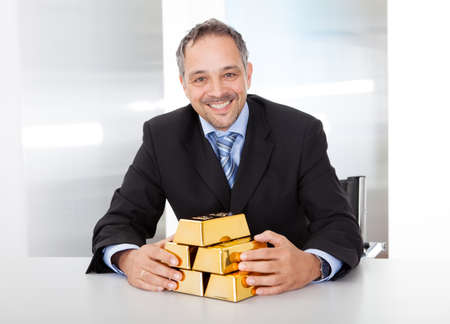 corporate greed: Portrait of happy businessman with golden bars at the office Stock Photo