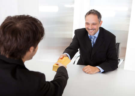corporate greed: Portrait of happy businessman receiving gold bar Stock Photo