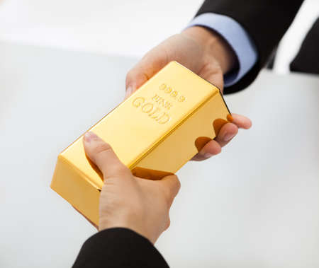 gold bars: Close-up on hand of business people exchanging golden bar Stock Photo