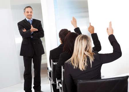 preguntando: Grupo de hombres de negocios exitosos en la conferencia haciendo preguntas
